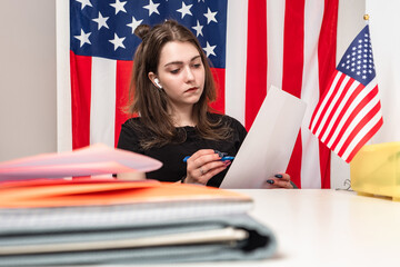 American businesswoman. A woman studies documents against the background of the us flag. Girl with documents next to the American flag. Work in America. Immigration to the USA.