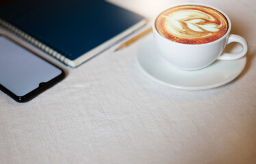 Close up latte coffee in white cup with smart phone and blue notebook on  white cotton cloth on the table