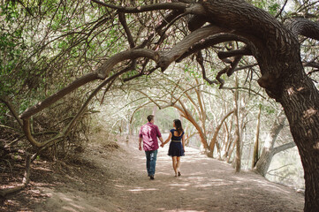 Engaged couple walking and holding hands under trees
