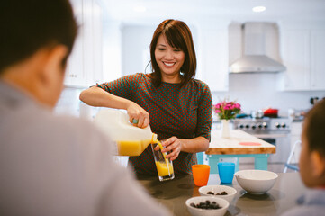 Mother smiles at family while pouring orange juice in kitchen Papier Peint
