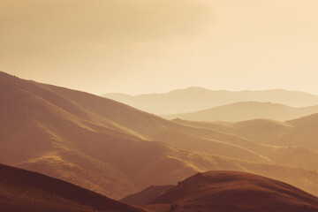 Spectacular landscape of bare mountains in the light of the sunset.