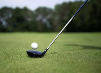 Golfer sets club in front of golf ball on tee