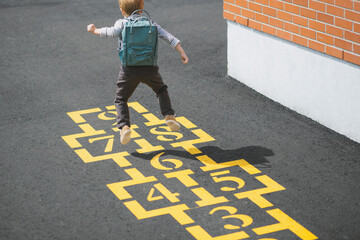 A boy skipping on the hopscotch at a school playground
