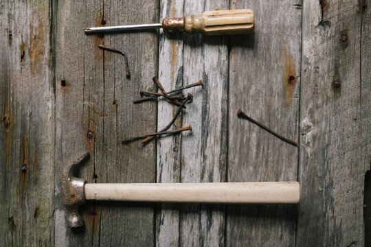 Old tools with rosty nails with the background of weather worn p