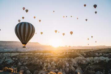 Air balloons racing over rocky terrain at dawn