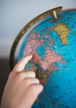 Child points to Canada on a globe