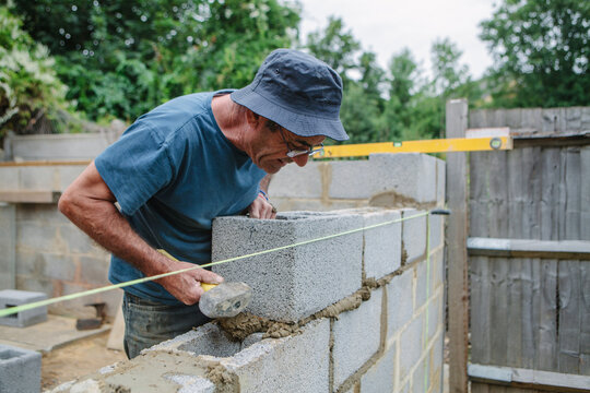 Builder working on a construction site building a wall