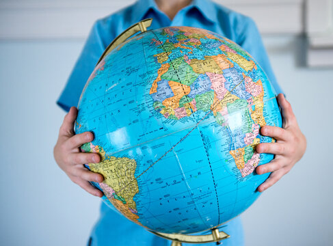 Boy holds a globe in his arms