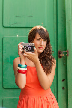 Woman taking pictures with retro camera.