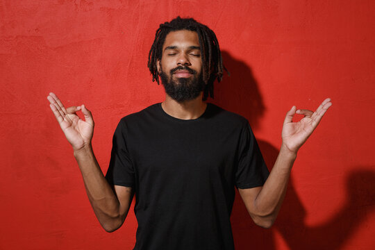 Relaxed young african american man guy 20s in black t-shirt posing hold hands in yoga gesture, relaxing meditating, trying to calm down keeping eyes closed isolated on red background studio portrait.
