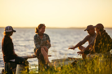 Family Sitting Around a Lakeside Campfire During Sunset