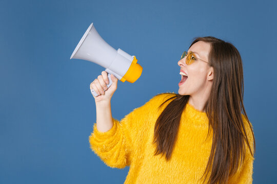 Excited beautiful cheerful funny young brunette woman 20s wearing yellow fur sweater eyeglasses posing screaming in megaphone looking aside up isolated on blue color wall background studio portrait.