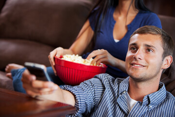 Television: Man Holds Remote Control While Watching TV