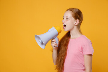 Little ginger redhead kid girl 12-13 years old wearing pink casual t-shirt posing screaming in megaphone and looking aside isolated on bright yellow color wall background children studio portrait.