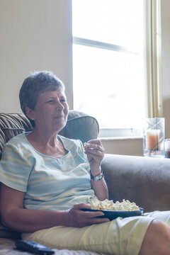 Woman Watches TV at Home on the Couch