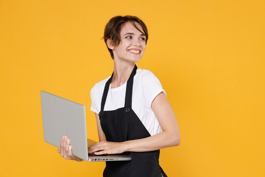 Smiling young female woman 20s barista bartender barman employee in white t-shirt apron posing working on laptop pc computer looking aside isolated on yellow color wall background studio portrait.