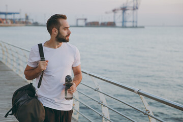 Portrait of handsome attractive young bearded athletic man guy 20s in white t-shirt with sports bag...