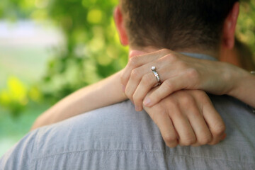 Back of male showing woman's hands with ring draped around his neck