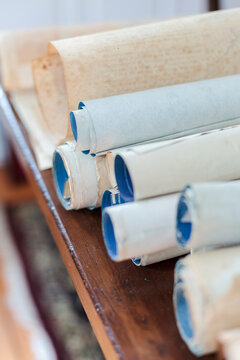 Antique scrolls lined up on a table.