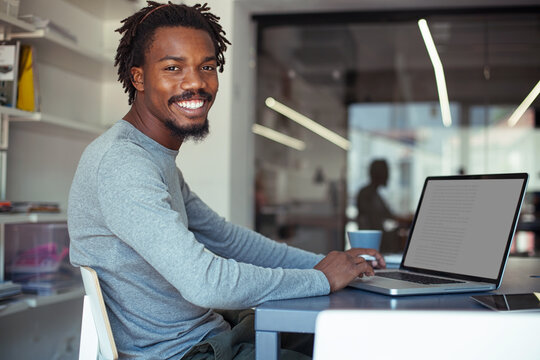 Smiling African Businessman at His Laptop