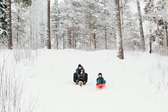 Father and Sons Riding Sleds Down Hill
