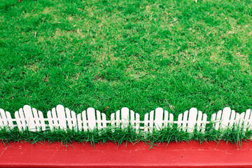 Image of a green lawn with white picket fencing and red pavement