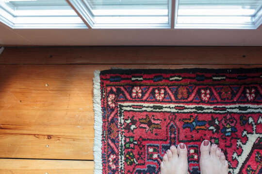 Looking down on a woman's feet standing on an oriental carpet.