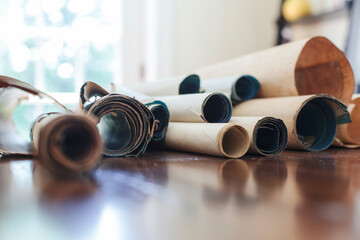 A pile of antique scrolls sit on a table.