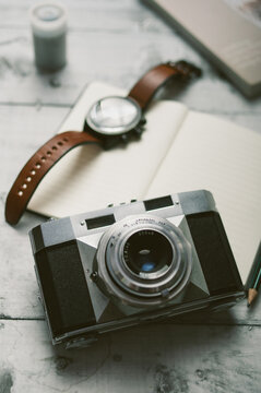 Analog Camera And Man's Wristwatch On The Desk