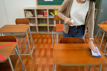 Young female teacher using an alcohol spray to disinfect student desks in classroom. Asian woman in...