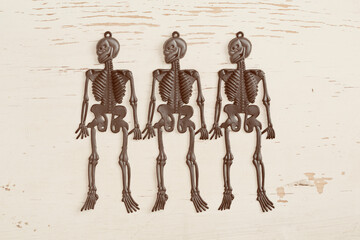 Plastic skeletons on old painted wood background