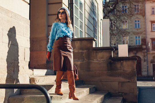 Portrait of stylish woman wearing sweater beret leather skirt in city. Autumn fashionable accessories and clothes.