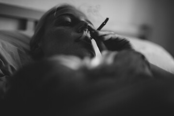 Woman smoking cigarette lying on the bed