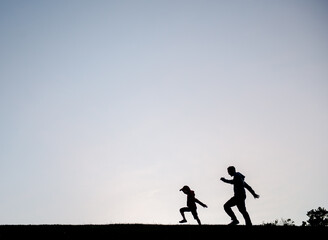 Silhouette of a father and son walking together across a field at sunset