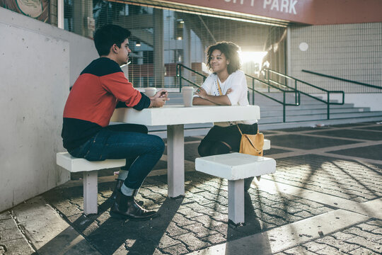 Young Couple Sitting in Urban Setting