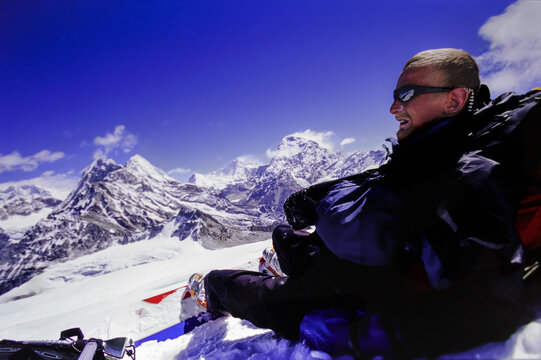 Snowboarder resting on snow during a big mountain descent in the Himalayas.