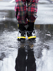 Child wearing rubber boots splashes in a rain puddle