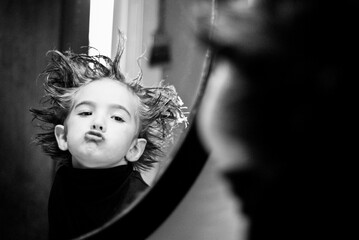 Boy with messy, spiked up hair makes a silly face in the bathroom mirror