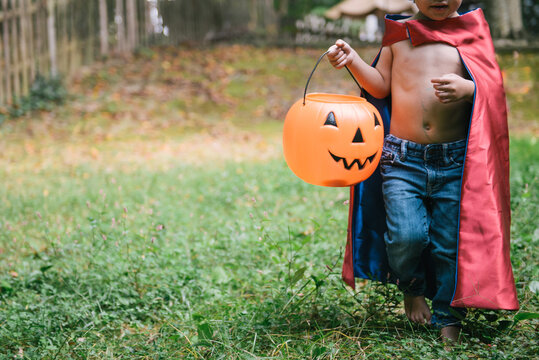 toddler in super hero cape costume is ready to go trick or treating for Halloween