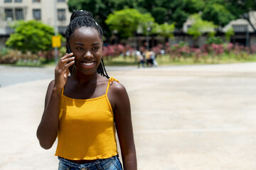 Afro american female young adult laughing at phone