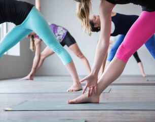 Women in a class at a yoga studio are in the extended triangle pose