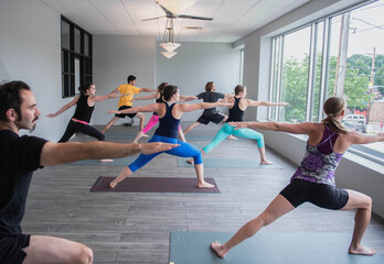 Men and women in warrior pose in a class at a yoga studio