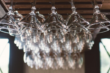 cocktail glasses hanging from the ceiling of a bar
