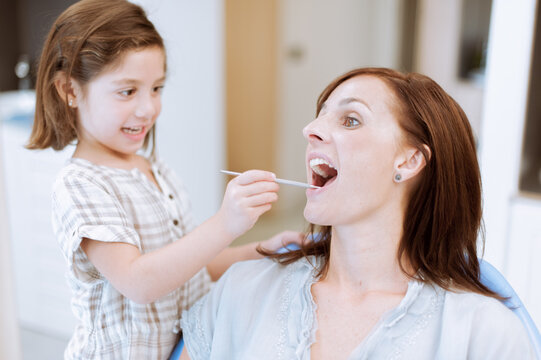 little girl playing to be a dentist with her mum