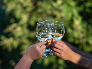 White wine glasses in hands. Two unrecognizable people clang glasses together outdoors.
