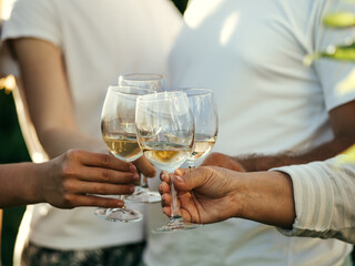 White wine glasses in hands. Four unrecognizable people clang glasses together outdoors.