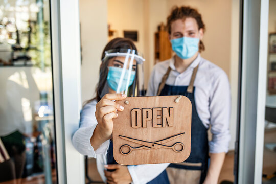 Happy business owners at a hairdressing studio hanging an open sign during COVID-19. Woman and man with surgical protective mask holding open sign in front of  small business store.