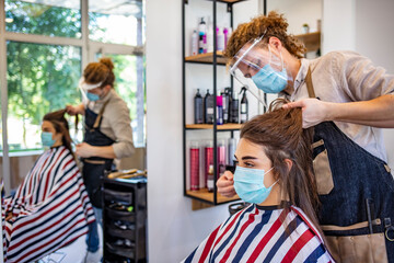 Adult woman at hairdresser wearing protective mask due to coronavirus pandemic. Woman in protective medical mask and hairdresser. Hairdressing salon opened! Covid-19, coronavirus .