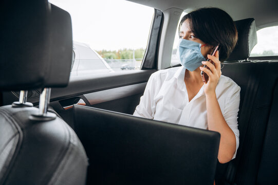 Quarantine time. Distant work. Business woman sitting in the car in the back seat wearing a protective mask and talks on the phone and working online using a laptop