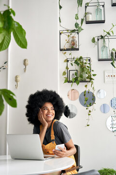 Young happy stylish African American gen z hipster lady student with Afro hair laughing, looking through window, sitting at table in modern cozy cafe interior, holding phone, using laptop.